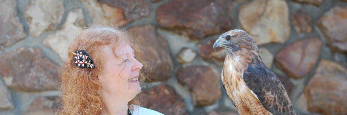 Volunteer Anne with red-tailed hawk Isham.