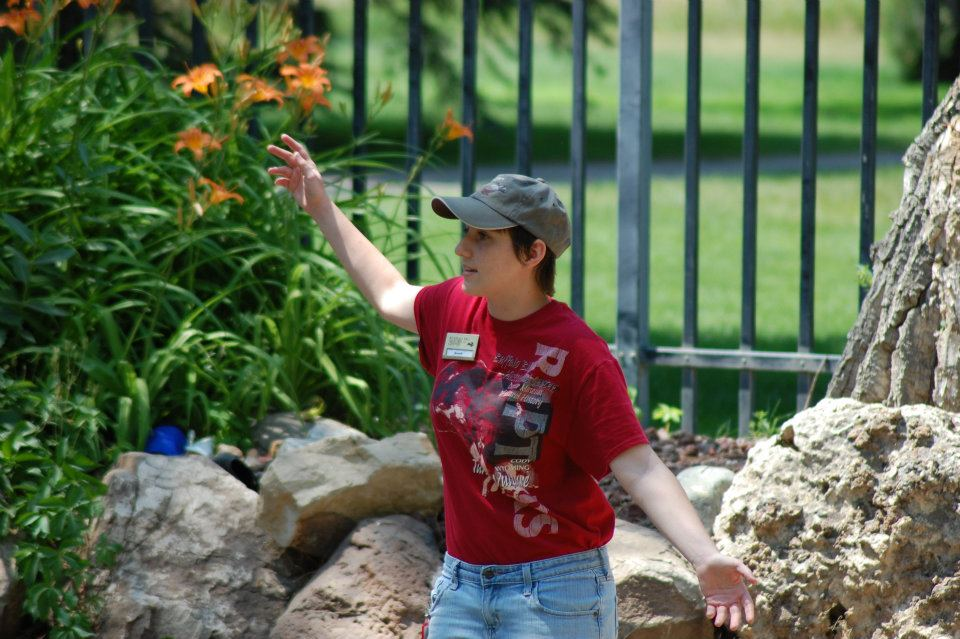 A trainer at the Greater Yellowstone Raptor Experience connecting with the audience by getting in touch with her inner bird.