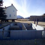 A new foundation, with the house approaching on the flatbed, January 2004.