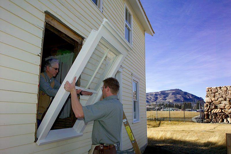Center carpenters installing restored windows.