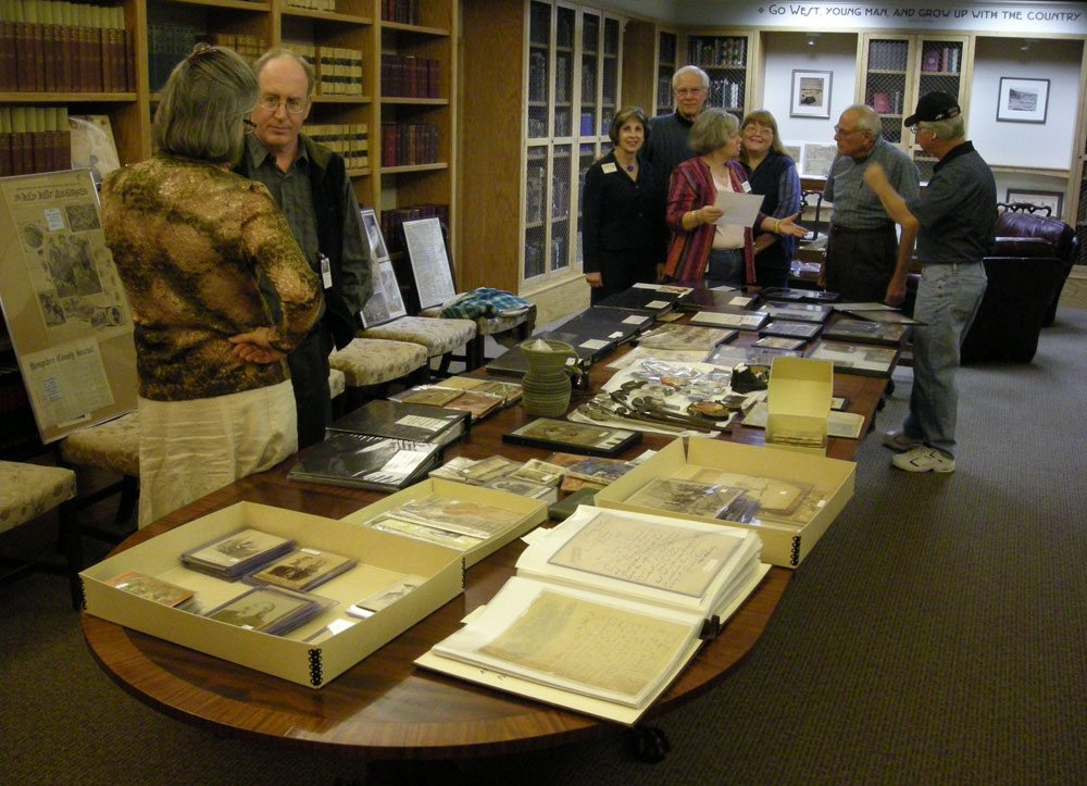 Library staff and advisory board members examine a new acquisition
