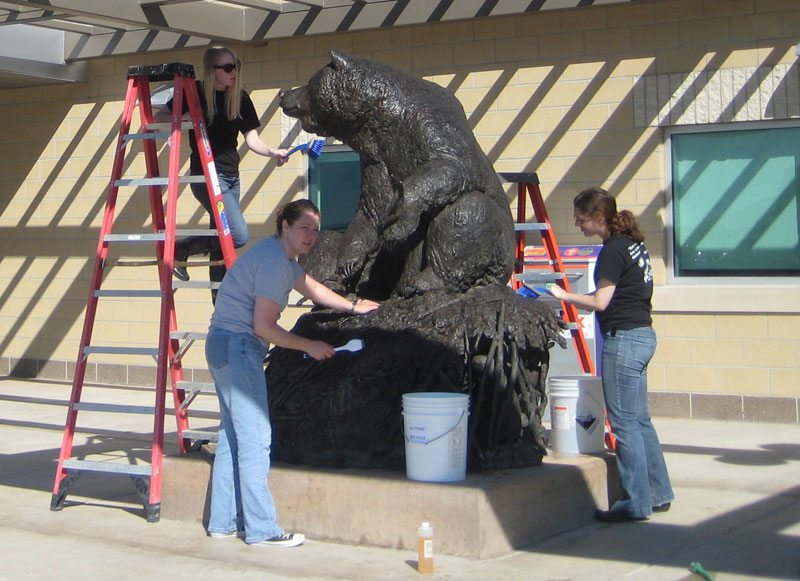 "Interns in the Center's Conservation Residency program clean ""Big Hal,"" a sculpture on loan to Yellowstone Regional Airport. ""Big Hal"" by Michael Coleman, modeled 2002, cast 2003. Gift of Jim and Kathy Taggart. 6.04"