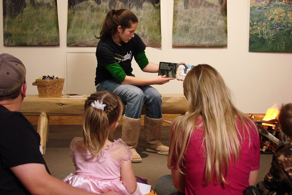 """Jordan, another new volunteer, reading """"Owl Babies"""" to a group of children and parents at our Halloween event."""
