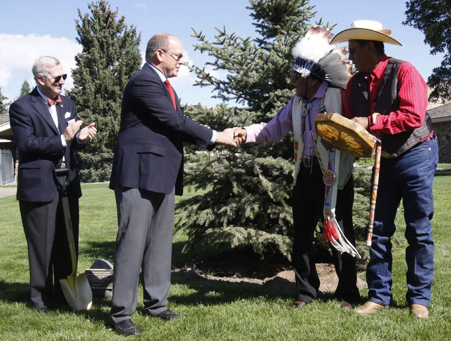 Prince Albert II of Monaco shaking hands with Crow elder Joe Medicine Crow