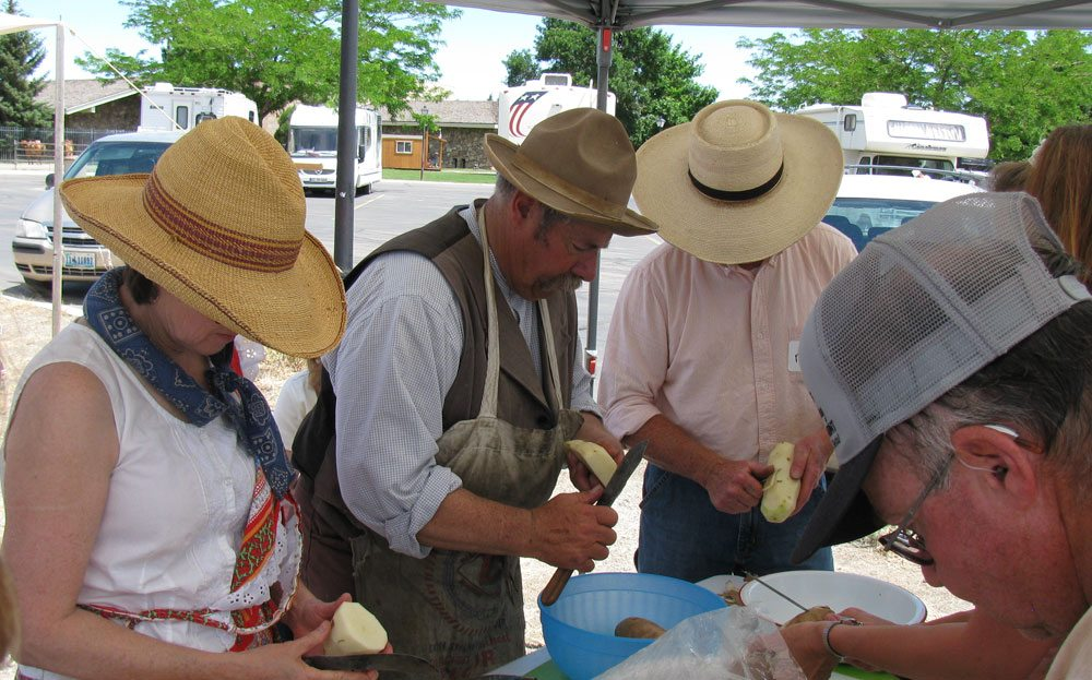 "Chuck wagon ""cookie"" Ron Reed and guests prepare potatoes for a recipe at a recent workshop."