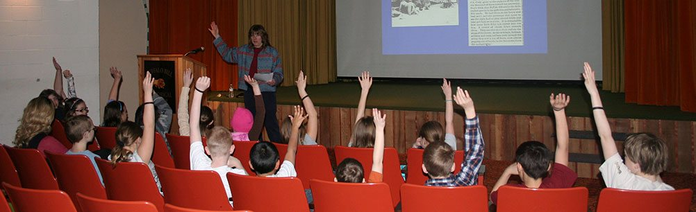 Students eagerly raise their hands to answer a question at a Museum Adventure