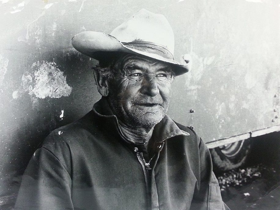 old man wearing cowboy hat leaning against trailer