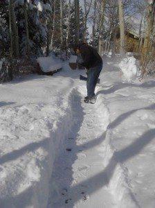 Man shoveling snow off the sidewalk.