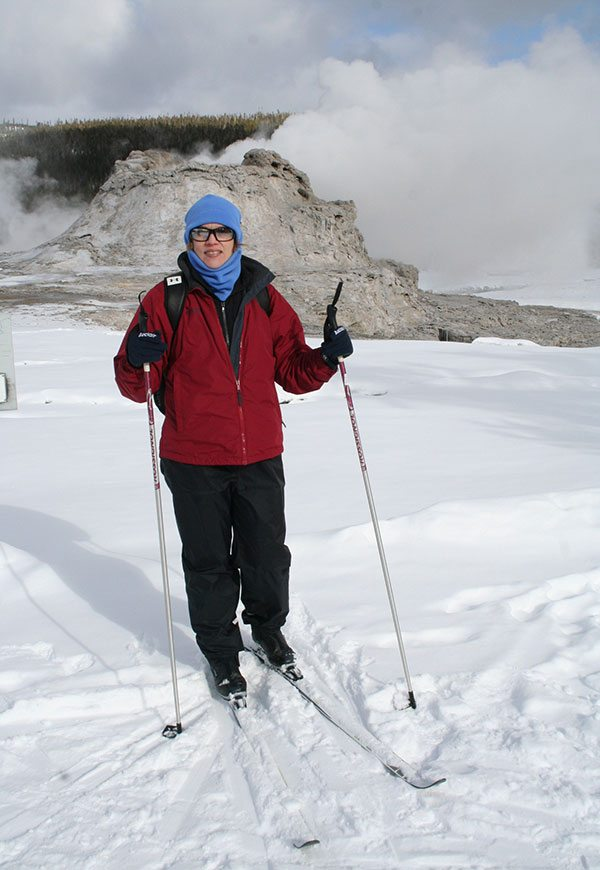 Nancy on skis in front of Castle Geyser, Old Faithful area in Yellowstone National Park