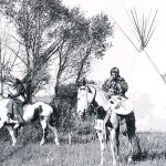 "Joseph Henry Sharp (1859 – 1953), ""Crow Indians on Horses in Tipi Village."" Black and white photograph."