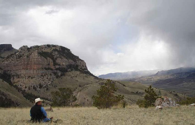 Research Assistant Richard Jones monitors a Golden Eagle nest on the distant ledge.