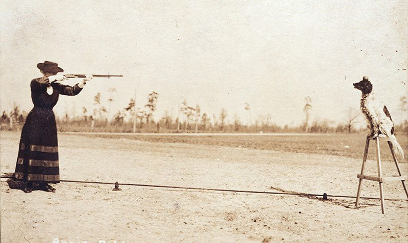 Annie Oakley plans to shoot an apple off the head of her dog Dave in this postcard image. P.94.1
