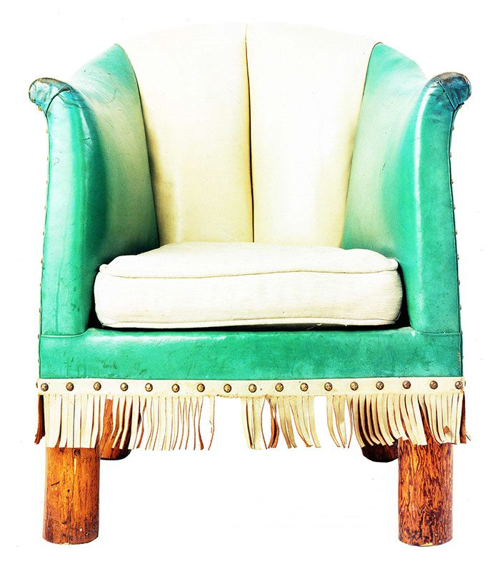 Barrel chair, green/white leather upholstered. Blue and white top-grain leather originally with leather-covered cushion, fringe trim. Collection of the Stonehouse Family