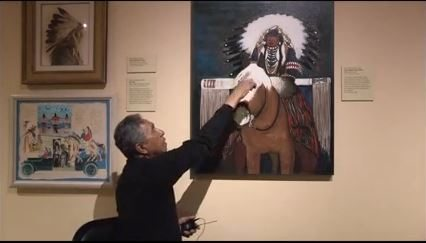 Kevin Red Star explains his color palette for the painting, Crow Indian Parade Rider