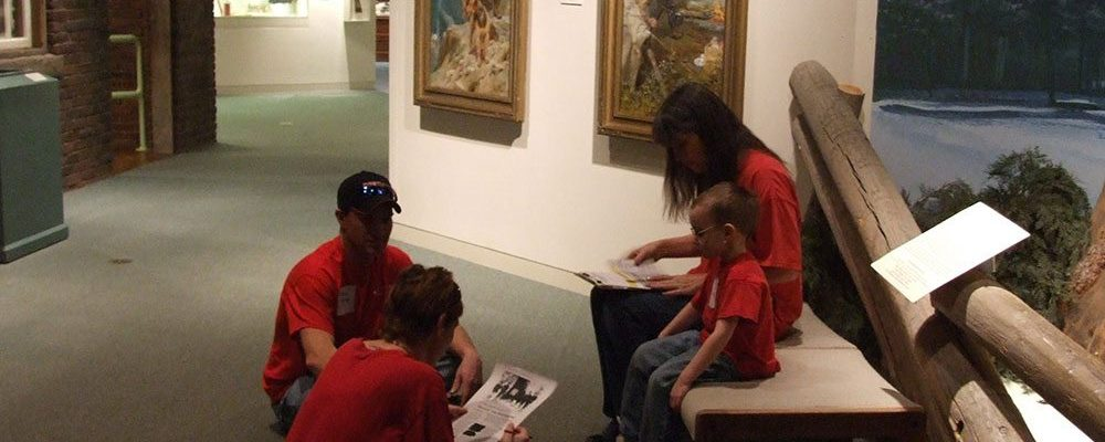 """A family strategizes its next move at a past """"'A Muzeum' Race"""" Family Fun Day."""
