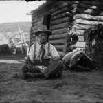 """Old Charlie Collins looks a bit """"worse for the wear"""" with his tin plate of trail vittles. Charles J. Belden, Charlie Collins, ca.1920, black and white glass plate negative. Gift of Mr. and Mrs. Charles Belden. PN.67.39"""
