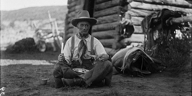 "Old Charlie Collins looks a bit ""worse for the wear"" with his tin plate of trail vittles. Charles J. Belden, Charlie Collins, ca.1920, black and white glass plate negative. Gift of Mr. and Mrs. Charles Belden. PN.67.39"