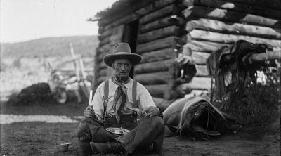 """Old Charlie Collins looks a bit """"worse for wear"""" with his tin plate of trail vittles, ca. 1920. Charles Belden black and white glass plate negative. Gift of Mr. and Mrs. Charles Belden. PN.67.39 (detail)"""