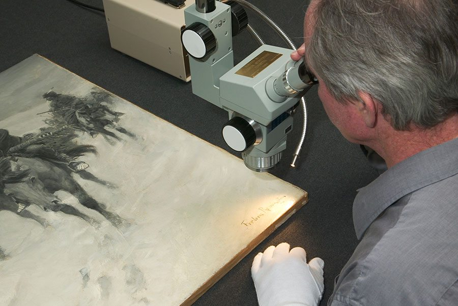 Illustration 4: Glenbow Museum painting conservator Don Murchison examines the signature under the microscope.