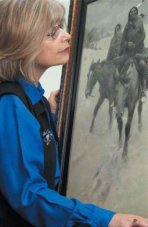 "Story author Monique Westra studies the Glenbow's ""Warriors'."""