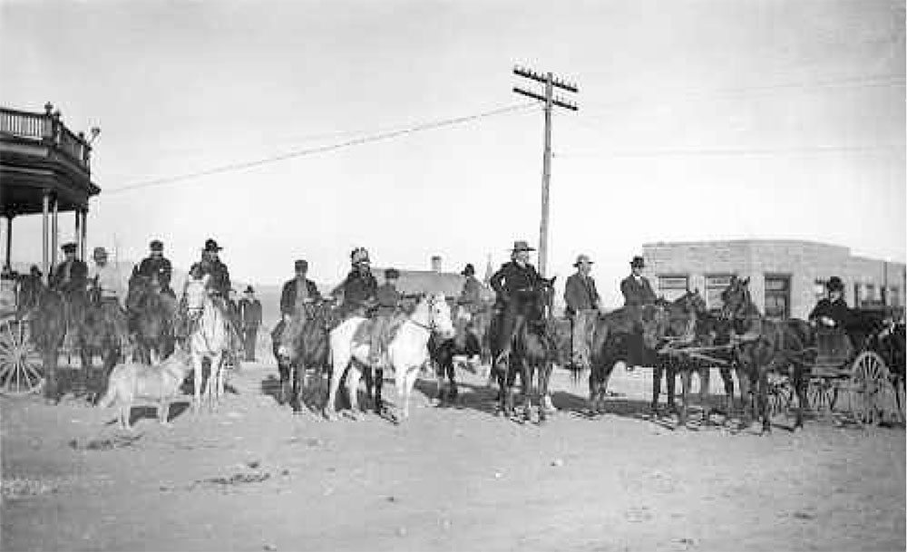 """Buffalo Bill and his so-called """"posse"""" - actually his hunting guests - in 1904, congregating in front of the Irma Hotel (left) with the First National Bank in the background. Courtesy Wyoming State Archives, State Parks and Cultural Resources. King Neg #596"""