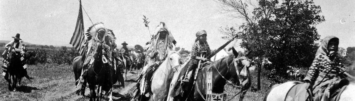 Horse and riders parading at Crow Fair, Crow Agency, Montana. Photo by W.H.D. Koerner, 1927. P.78.4452 (detai)