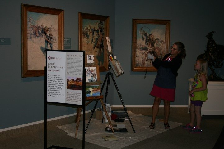 Farrier demonstrating her work to a young visitor in the Whitney Western Art Museum.