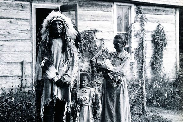Standing Bear, Rose Two Bonnets, Lula Two Bonnets, and Louisa Standing Bear in front of their home, 1919. Photograph courtesy of Arthur Amiotte.