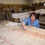 Buffalo Bill Center of the West Conservator Beverly Perkins works on a painted hide from the Plains Indian Museum collection.