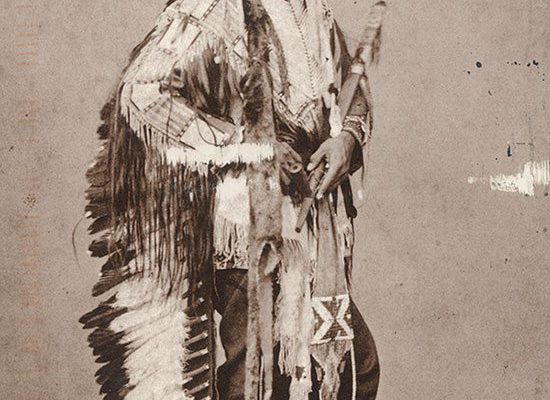 Black and white postcard. Touch the Clouds wearing war bonnet and traditional regalia. Photo attributed to Julius Ulke. The Paul Dyck Plains Indian Buffalo Culture Collection, acquired through the generosity of the Dyck family and additional gifts of the Nielson Family and the Estate of Margaret S. Coe. P.320.429