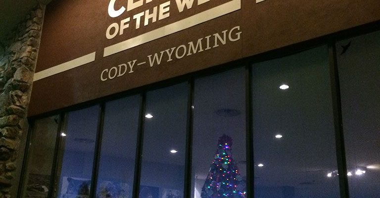 The Buffalo Bill Center of the West's lighted Christmas tree shines through the buildings front facade.