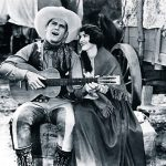 "Cowboy movie star Ken Maynard singing to his co-star Edith Roberts in the 1929 Universal Maynard production ""The Wagon Master"" (Saturday Matinee)."