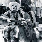 """Cowboy movie star Ken Maynard singing to his co-star Edith Roberts in the 1929 Universal Maynard production """"The Wagon Master"""" (Saturday Matinee)."""