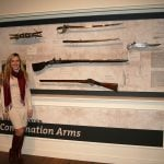 "Cody Firearms Museum Curator Ashley Hlebinsky reviews labels in the Combination Arms section of ""Journeying West: Distinctive Firearms from the Smithsonian"" at the Buffalo Bill Center of the West."