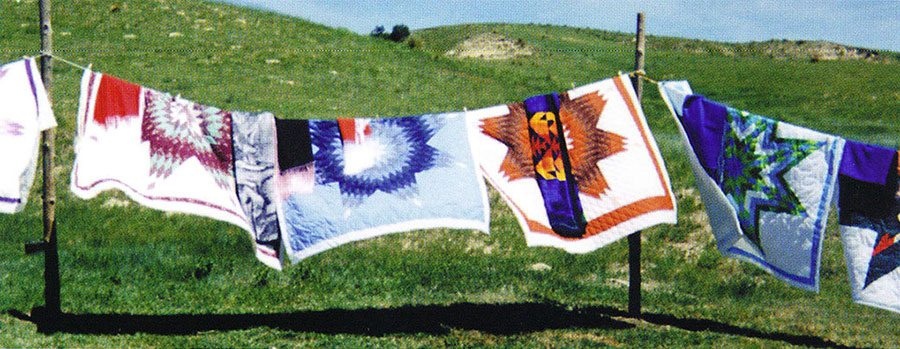 Blowing quilts at a memorial giveaway for Max Mesteth, brother of Freda Goodsell, Manderson, South Dakota. Quilts by Freda Goodsell. August 24, 2000. Photo by Arthur Amiotte.