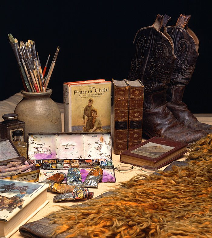 """W.H.D. Koerner's paints, brushes, artist's materials, cowboy boots, wooly chaps, """"The Prairie Child,"""" """"North of 36,"""" """"Ruskin's Modern art,"""" and """"What is Art."""" All from W.H.D. Koerner Studio Collection. Gift of the artist's heirs, W.H.D. Koerner III and Ruth Koerner Oliver."""