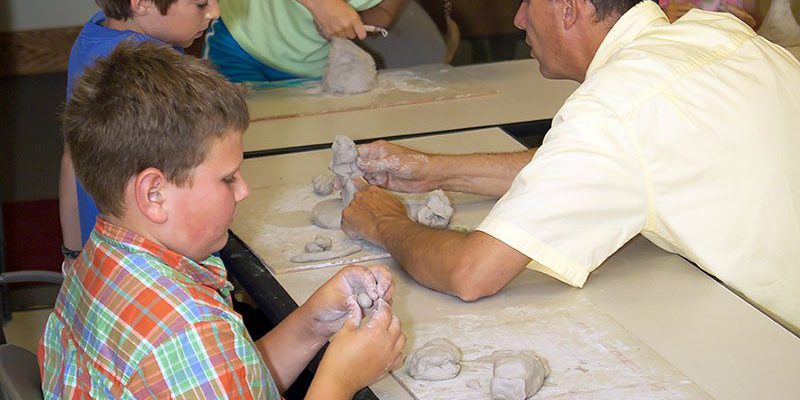 Jeff Rudolf teaching kids to sculpt with clay.