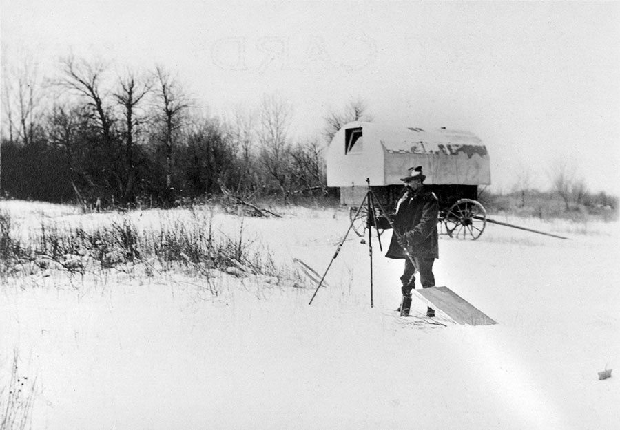 """""""Setting up, 'Prairie Dog' in background, Crow Agency, Mont. ca. 1900."""" Artist Joseph Henry Sharp was also a photographer. This print shows him setting up his easel in the snow, with his covered wagon studio that he nicknamed """"Prairie Dog"""" behind him. P.22.42"""