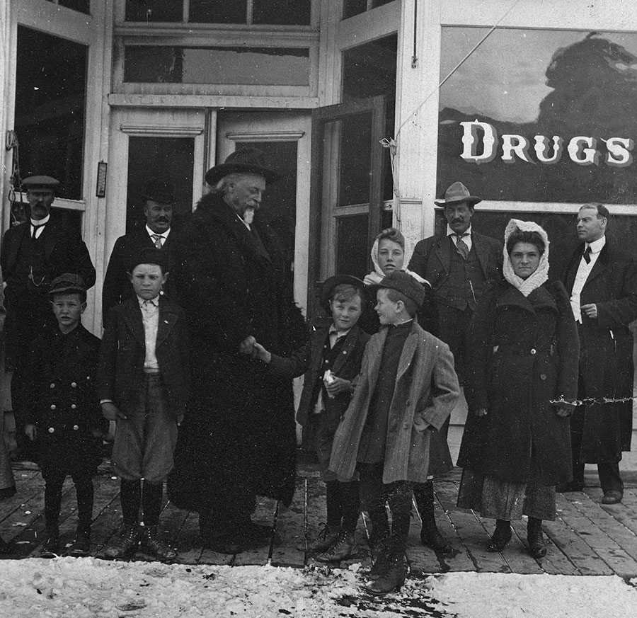 Youngsters loved Buffalo Bill. Here he shakes hands with a young admirer in front of the Meeteetse, Wyoming, drugstore, ca. 1913. MS6 William F. Cody Collection, McCracken Research Library. P.69.1153