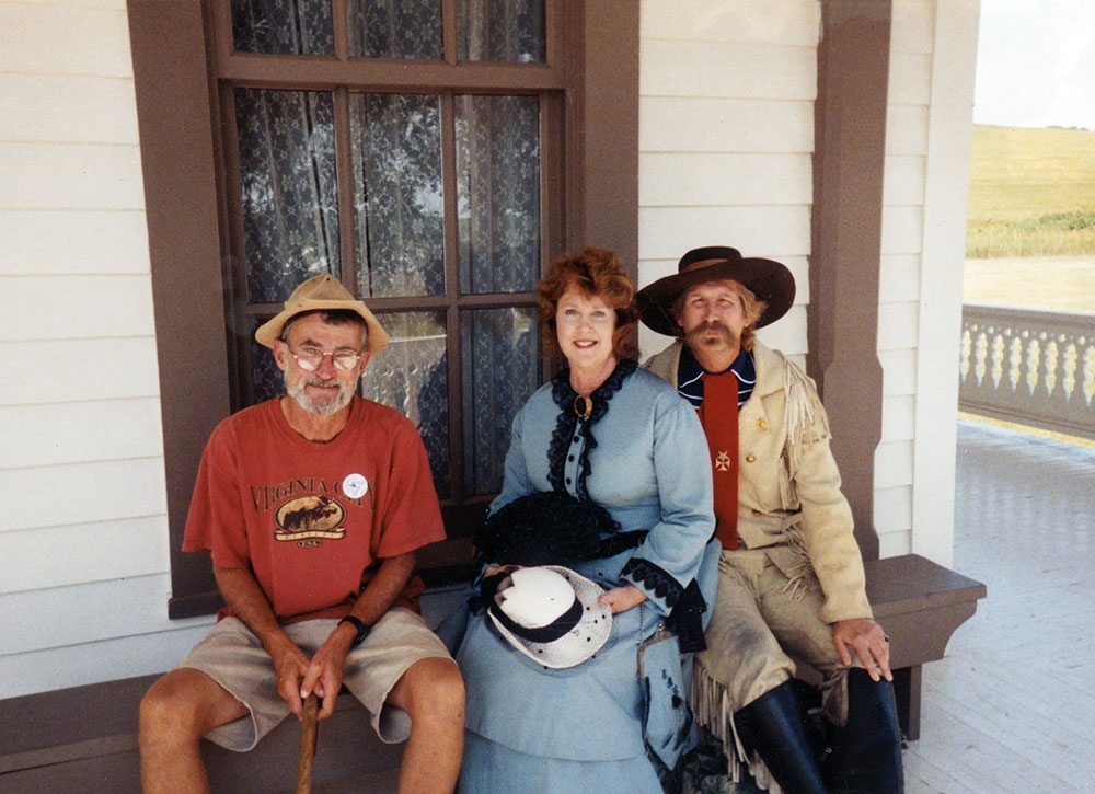 """The """"Charming Bum,"""" Guy Gertsch (left), visits with Libby and George Armstrong """"Autie"""" Custer outside their reconstructed home at Fort Abraham Lincoln near Bismarck, North Dakota."""