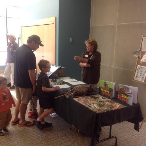 Lynn manning the Learning Table with lots of items to touch and read.