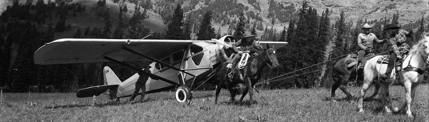 Lucille Nichols, on her father's white horse, leads riders tugging on Bill Monday's plane. MS3 Charles Belden Collection. PN.67.838b