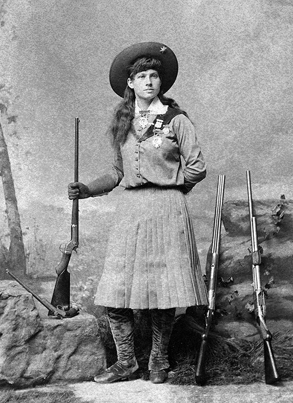 Annie Oakley poses with rifles and pistol. MS6 William F. Cody Collection. P.69.1164