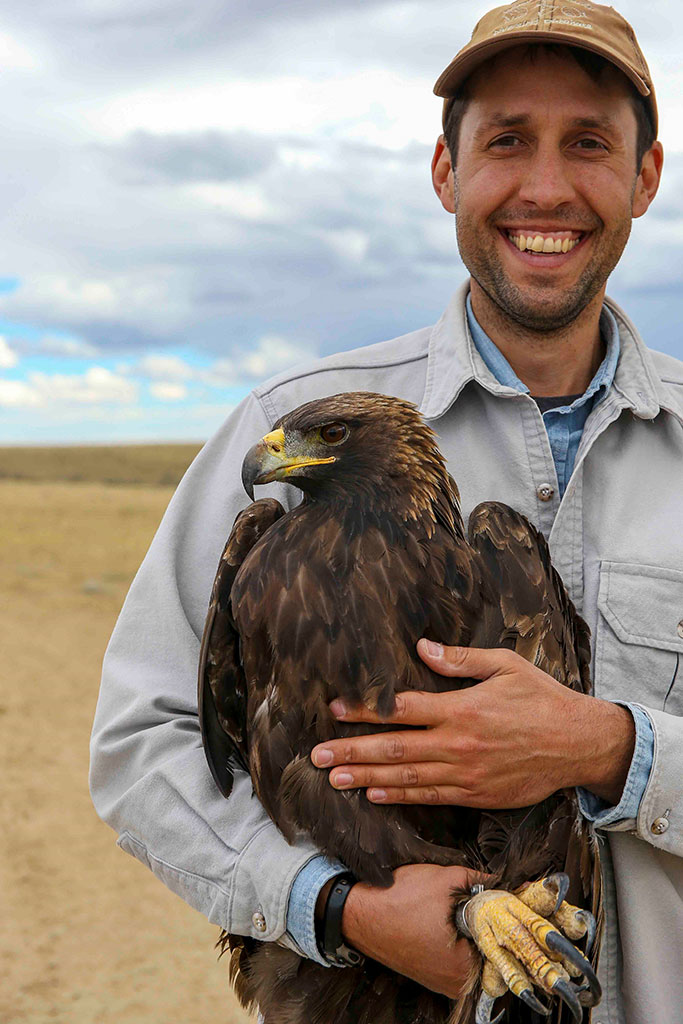 Zach Wallace in the field with a golden eagle. Photo by Mike Lockhart.
