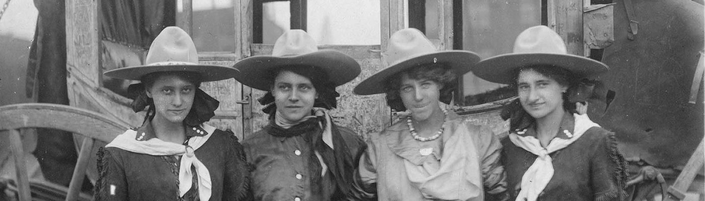 Four cowgirls posing in front of a stagecoach for the 101 Ranch Show, ca. 1916. Sepia toned photograph. MS 6 William F. Cody Collection, McCracken Research Library. P.69.1289 (detail)