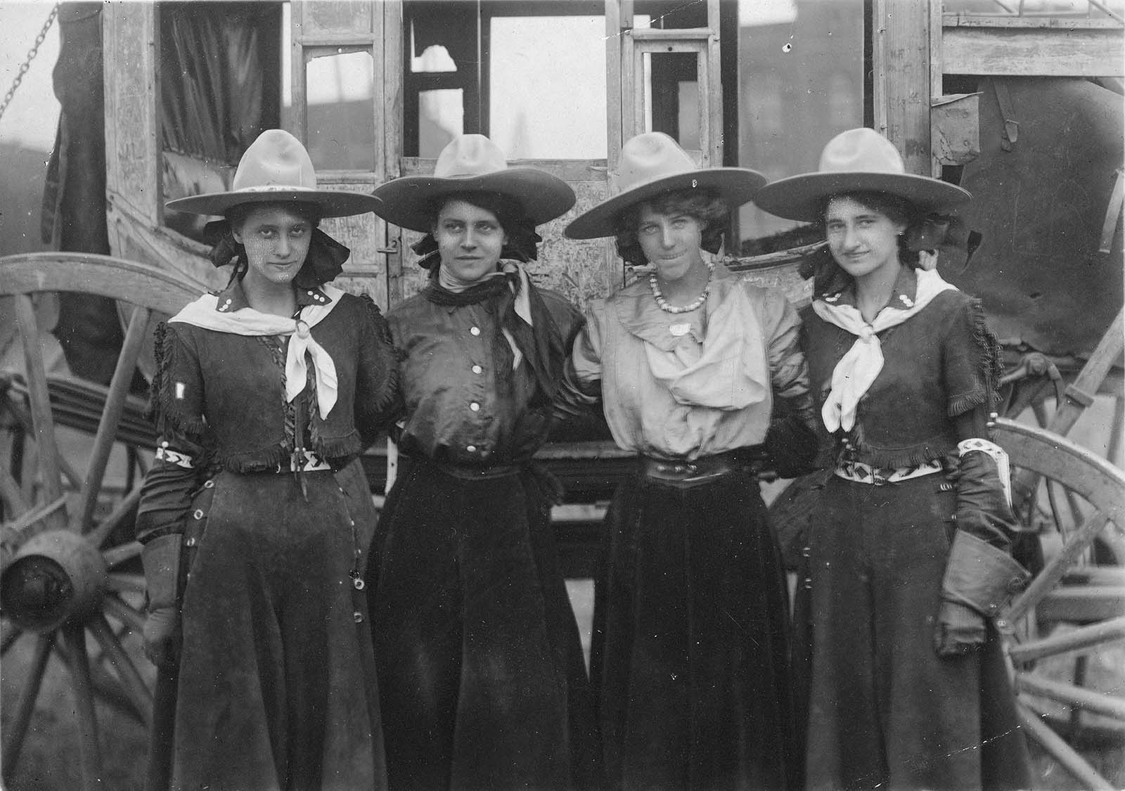 Four cowgirls posing in front of a stagecoach for the 101 Ranch Show, ca. 1916. Sepia toned photograph. MS 6 William F. Cody Collection, McCracken Research Library. P.69.1289