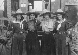 Four cowgirls posing in front of a stagecoach for the 101 Ranch Show, ca. 1916. Sepia toned photograph. MS 6 William F. Cody Collection. P.69.1289
