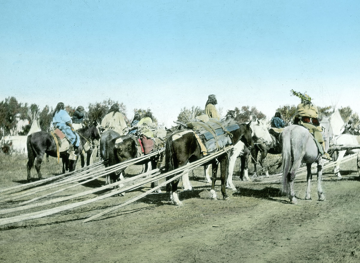 Several Crow people on horseback dragging tipi poles, ca. 1903-1925. MS 95 William A. Petzoldt Lantern Slide Collection. LS.95.294