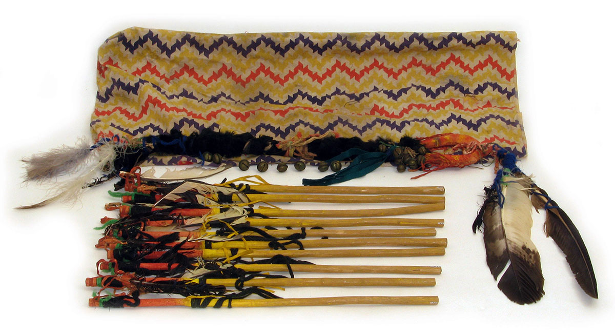Hand game rattle with game sticks and carrying bag. Hide, feathers, leather, yarn, brass bells, wool cloth. The Paul Dyck Plains Indian Buffalo Culture Collection, acquired through the generosity of the Dyck family and additional gifts of the Nielson Family and the Estate of Margaret S. Coe. NA.503.36