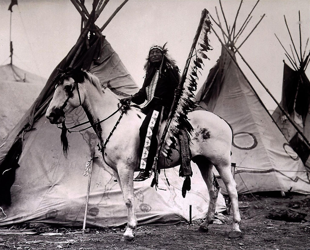 Iron Tail on his horse with tipis. Iron Tail became a close friend of Cody's, performing with the Wild West as well as accompanying him on hunts and other pleasure trips. MS 71 Vincent Mercaldo Collection. P.71.658
